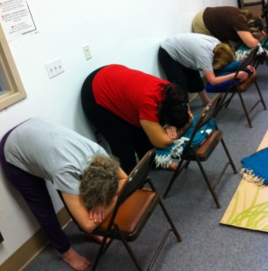 These students demonstrate how supported uttanasana can be adapted to varying flexibilities, from the most flexible in the foreground to least so on the far right in back. The student on the far right has had a hip replacement and spinal surgery.