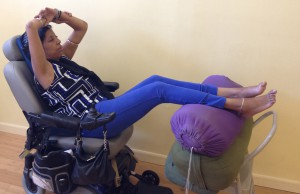 A sticky mat rolled up behind her spine, Lesley works on a version of upward arms in supine mountain pose.